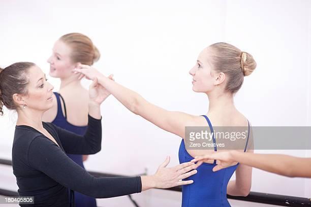 Teacher adjusting teenage ballerinas arm pose