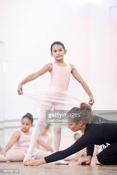 Teacher adjusting young ballerinas pose