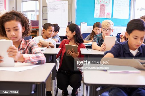 Teacher among kids with computers in elementary school class : Stock Photo