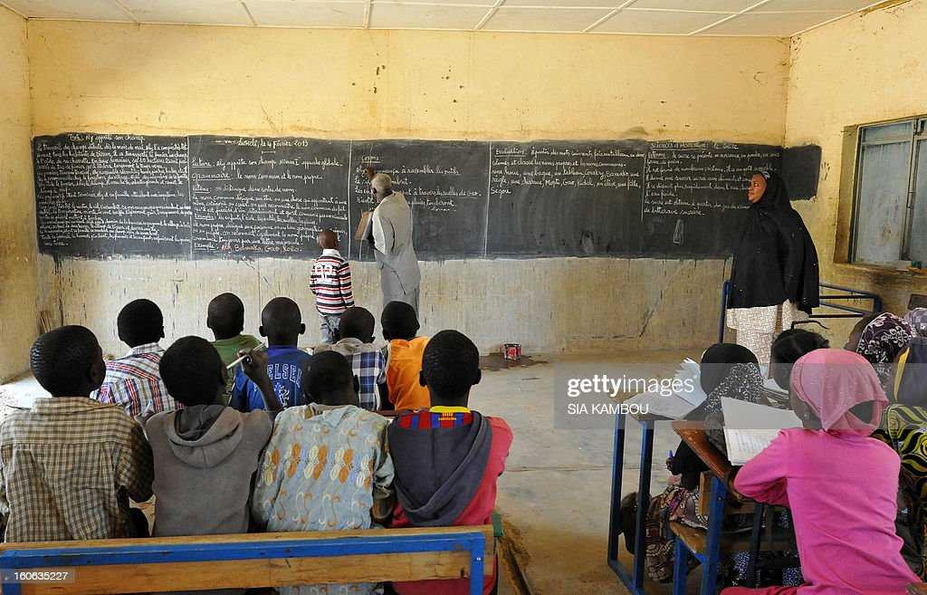 A teacher and a student stand at the blackboard as other students look on in a classroom in Gao, in the north of Mali, on the first day of the reopening of schools after the French bombing of Islamist targets, on February 4, 2013. Schools reopened today in Gao after the town was taken on January 26 by French and Malian forces from Islamists who had been occupying it for the last year.