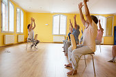 Teacher and active senior women yoga class on chairs, arms raised,