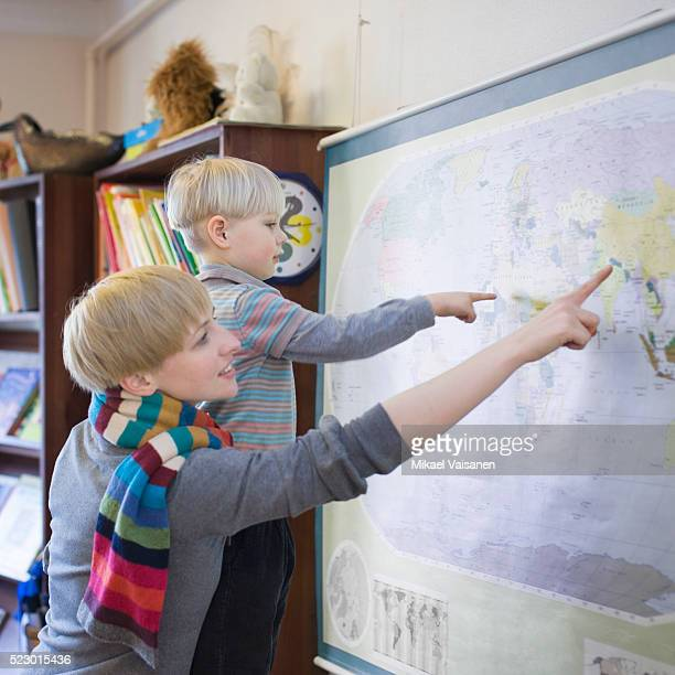 Teacher and boy pointing at map