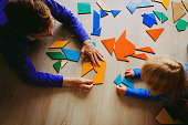 teacher and child playing with geometric shapes in school or daycare