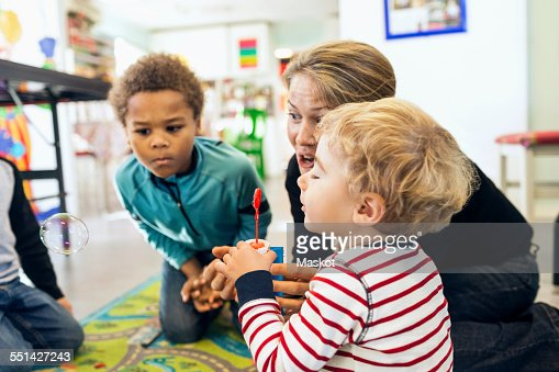 Teacher and children playing with bubbles in kindergarten