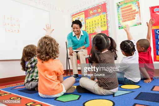 Teacher and children sitting on floors with hands raised : Stock Photo