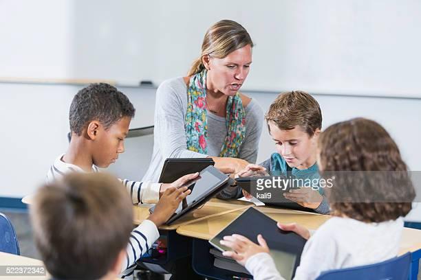 Teacher and elementary school children, digital tablets
