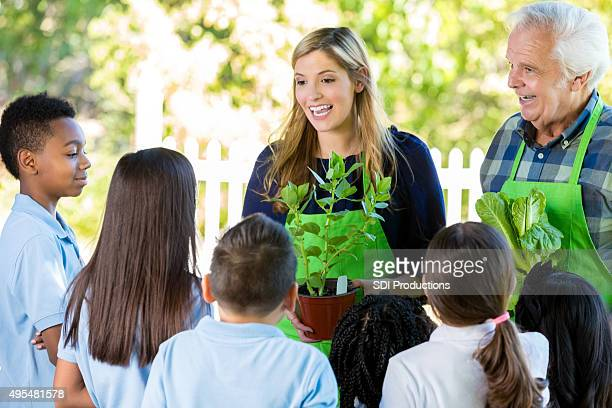 Teacher and farmer teaching elementary students about gardening
