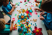 teacher and kids making origami crafts with paper, learning through play