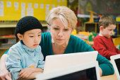 Teacher and kindergarten student looking at laptop