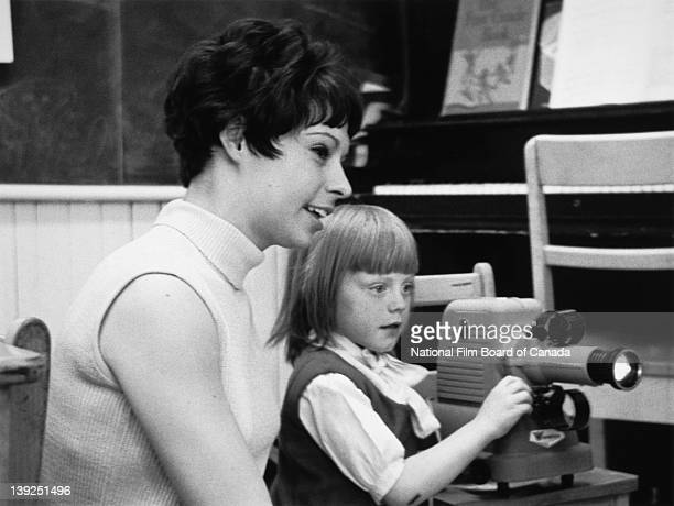 A teacher and one of her pupils look at the images projected by the filmstrip projector that the schoolgirl is operating in a classroom of the Lorne...