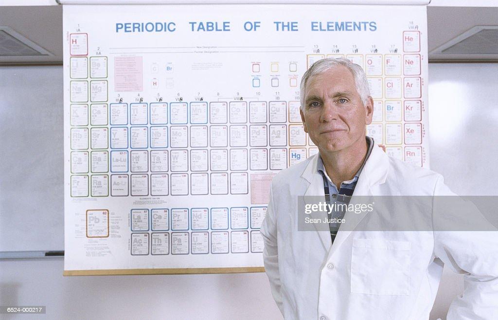 Teacher and Periodic Table : Stock Photo
