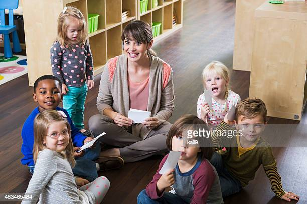 Lehrer und preschoolers auf dem Boden sitzen im circle