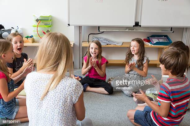Teacher and pupils sitting on floor of their classroom singing and clapping hands