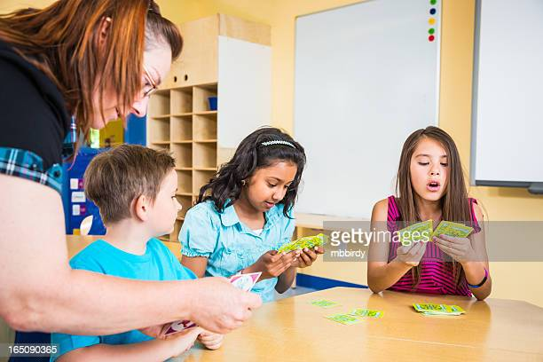 Teacher and school children playing card game