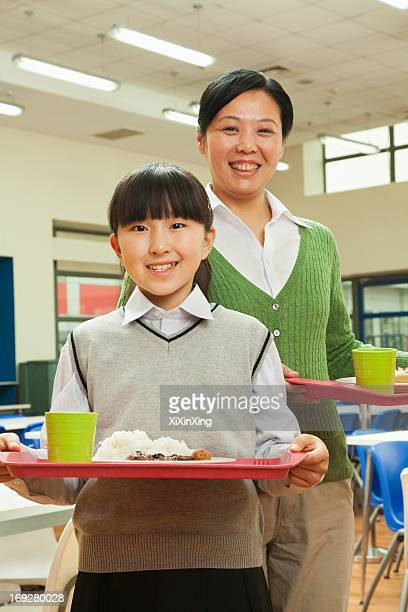 Teacher and school girl portrait in school cafeteria