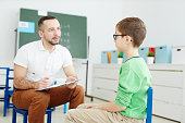 Confident school psychologist with document making notes while talking to schoolboy in classroom