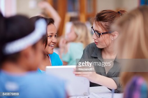Teacher and schoolgirls with digital tablet
