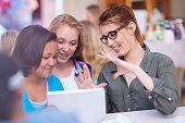 Teacher and schoolgirls with digital tablet