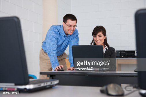 Teacher and student in computer lab : Stock Photo