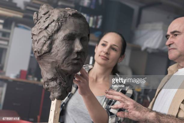 Teacher and student sculpting clay face