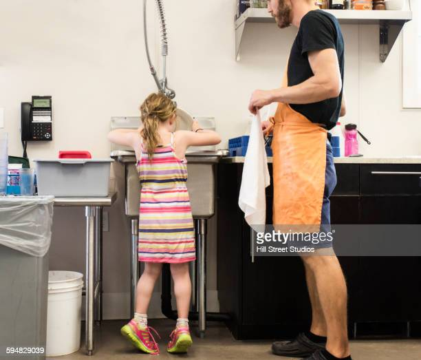 Teacher and student washing dishes in kitchen