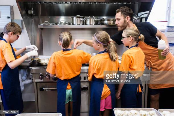 Teacher and students cooking in class