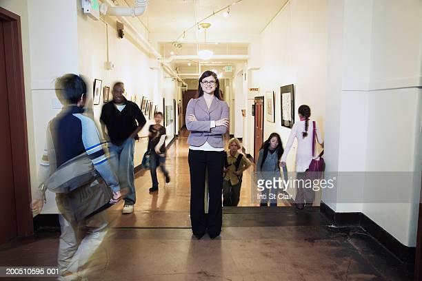 Teacher and students (9-13) in school corridor (focus on teacher)