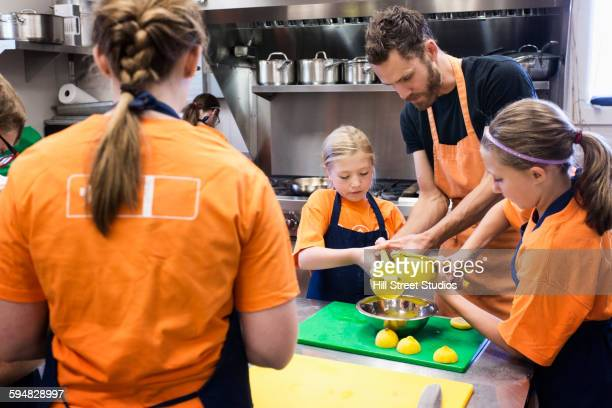 Teacher and students juicing fruit in cooking class