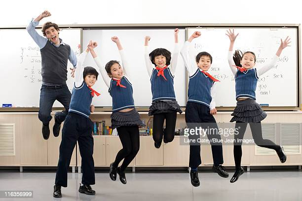Teacher and students jumping in front of whiteboard