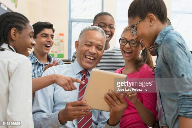 Teacher and students using digital tablet in classroom