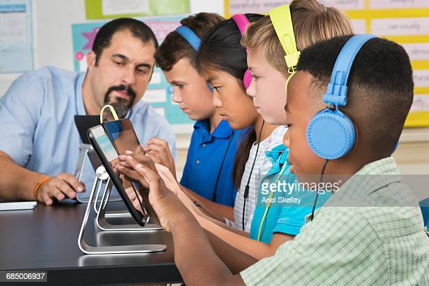 Teacher and students using digital tablets and headphones in classroom