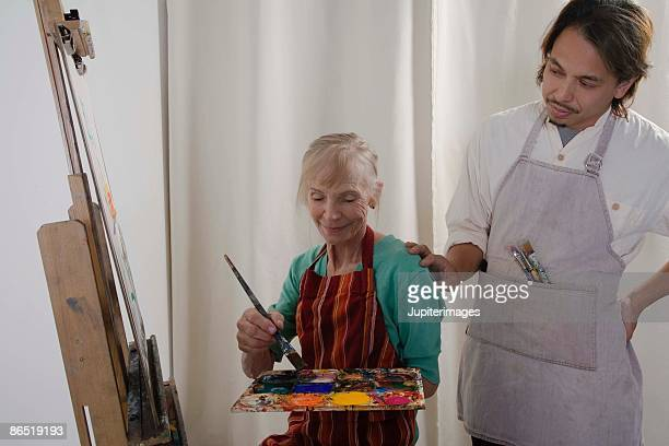 Teacher and woman painting