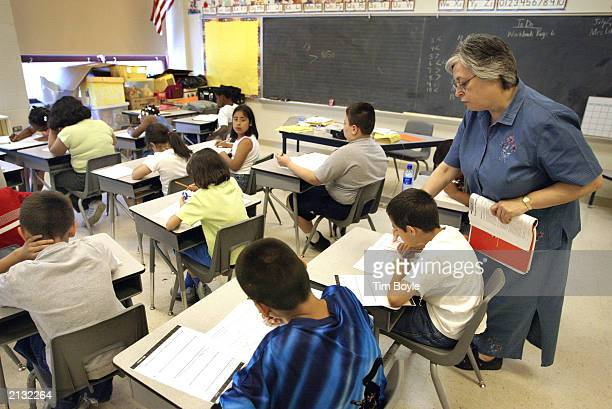 Teacher Arlene Lebowitz assists a student in her thirdgrade class during summer school July 2 2003 in Chicago Illinois A record number of students...