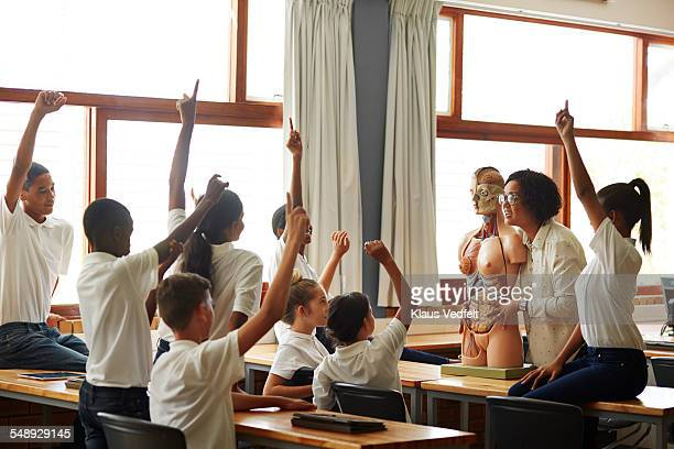 Teacher asking question to students w. rased hands