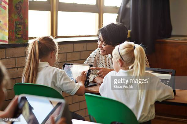Teacher assisting girls with tablets
