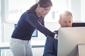 Teacher assisting mature student in computer room at college