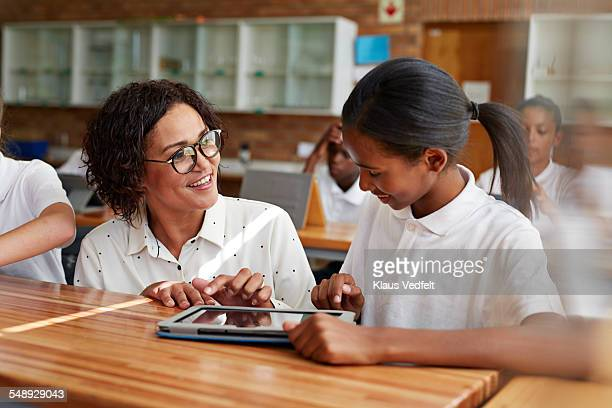 Teacher assisting school with tablet in class