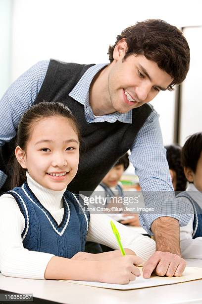 Teacher assisting student in class