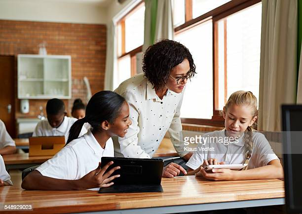 Teacher assisting students with tablets in class