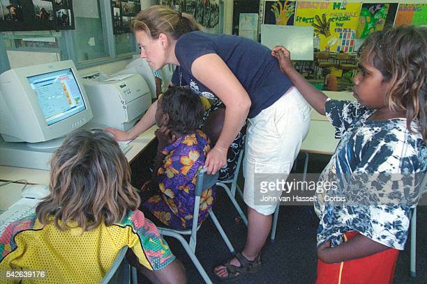 A teacher assists aboriginal pupils to use computers at a community school | Location Haasts Bluff Northern Territory Australia