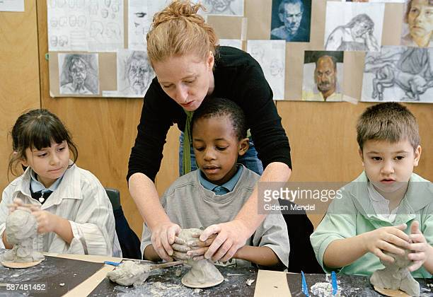 A teacher at Millfields Community School works with a group of pupils during a special sculpture workshop held for 'gifted and talented' children...