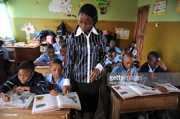 Teacher Bosede Omoniyi helps Omoze Ogwogho during class on June 6 2013 at the Christower International Schools one of Nigeria's private schools in...