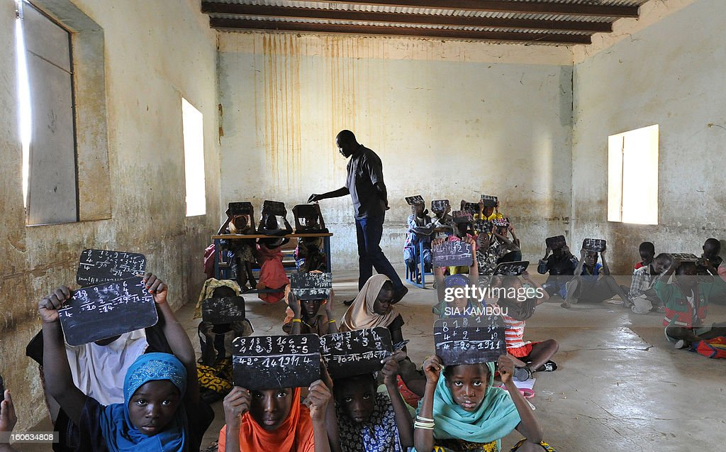 A teacher checks students' chalk boards in a classroom whose majority of tables and benches were taken by Islamists, on the first day of the reopening of schools after the French bombing of Islamist targets, on February 4, 2013 in Gao, in the north of Mali. Schools reopened today in Gao after the town was taken on January 26 by French and Malian forces from Islamists who had been occupying it for the last year.