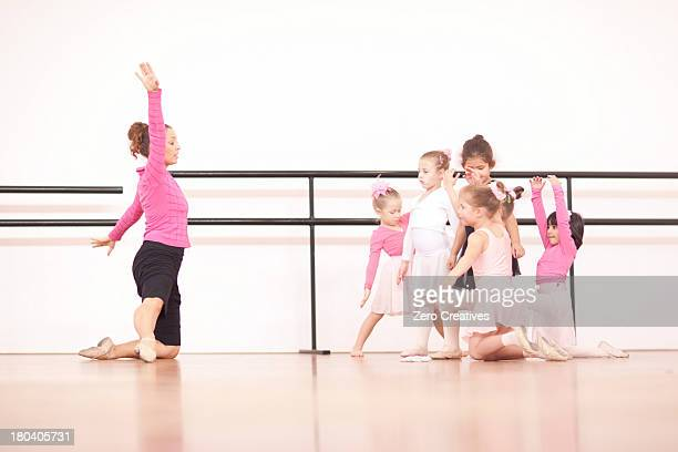Teacher demonstrating to a group of young ballerinas