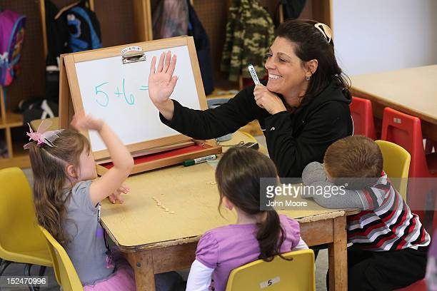 Teacher Denise Severing congratulates a child during a math lesson at the federallyfunded Head Start school on September 20 2012 in Woodbourne New...