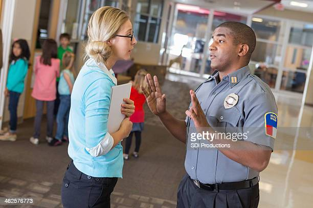 Teacher discussing saftey procedures with security officer in elementary school