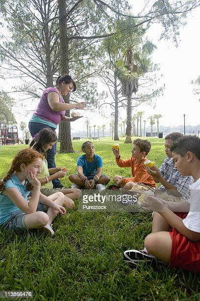 Teacher distributing cupcakes to children seated in a circle at a park