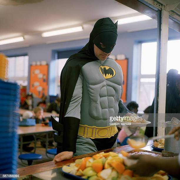 A teacher dressed as Batman for 'Come as your favorite book character' day takes a school dinner at Kingsmead Primary School The school primarily...