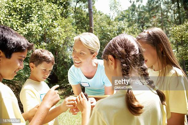 Teacher explaining about pine seeds to students on field trip