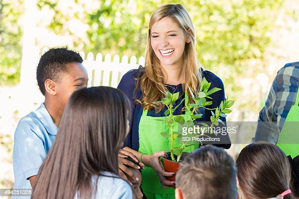 Teacher explaining gardening to elementary student during farm field trip
